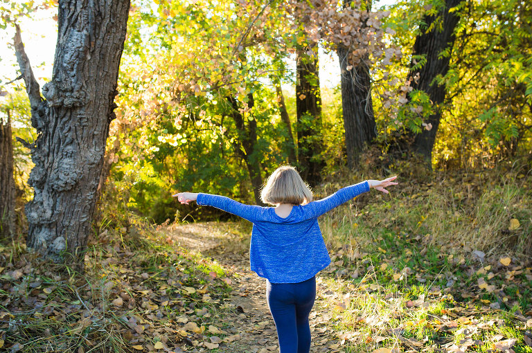girl with outstretched arms in woods - documentary family photography
