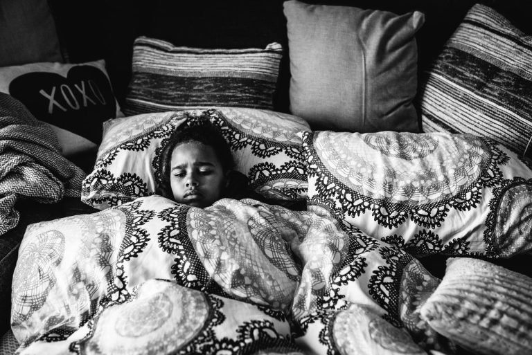 girl snuggled in bedding - documentary family photography