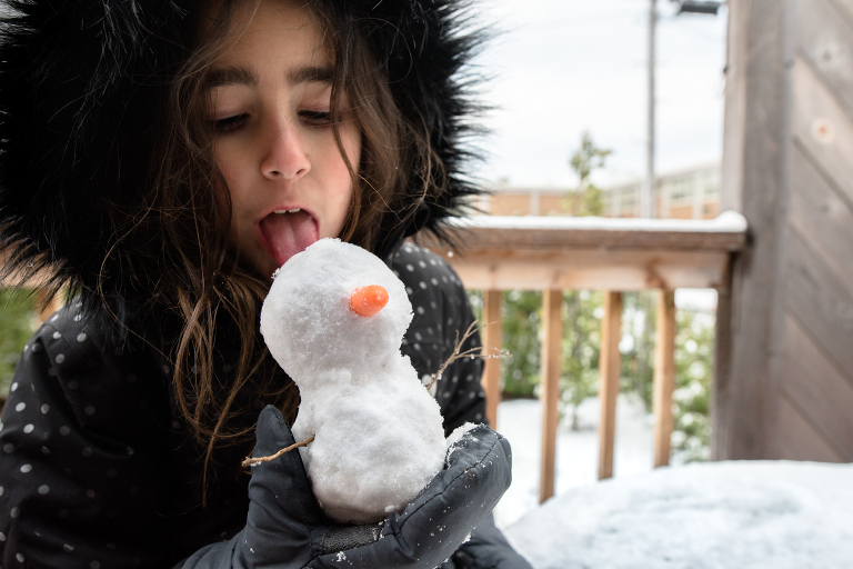 girl with mini snowman - documentary family photography