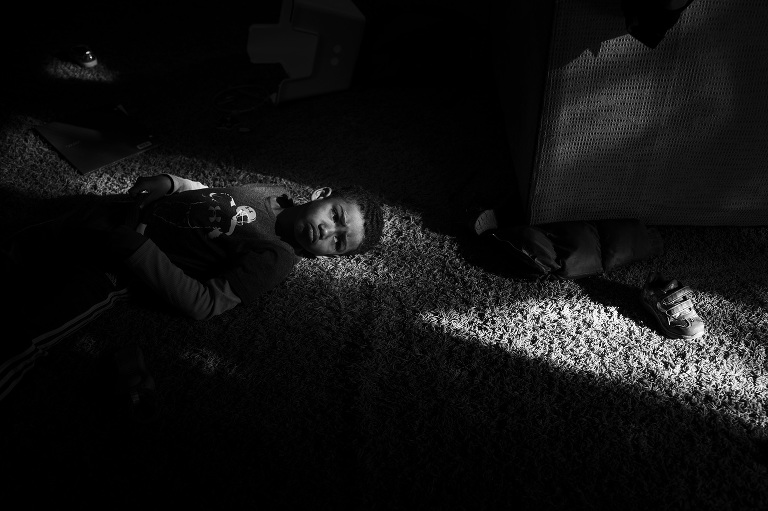 child laying in patch of sunlight - Documentary Family Photography