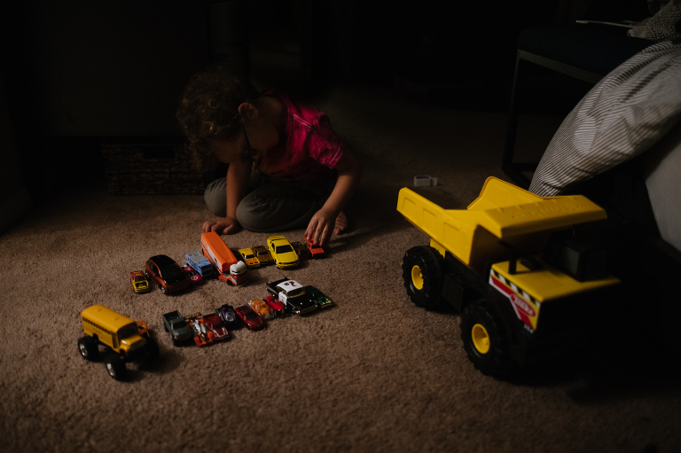 child lining up toy cars - Documentary Family Photography