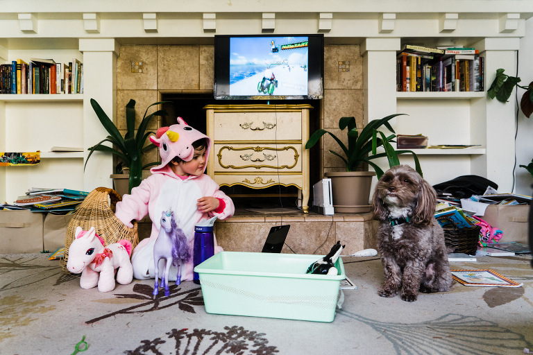 girl in unicorn costume stares at dog - Documentary Family Photography