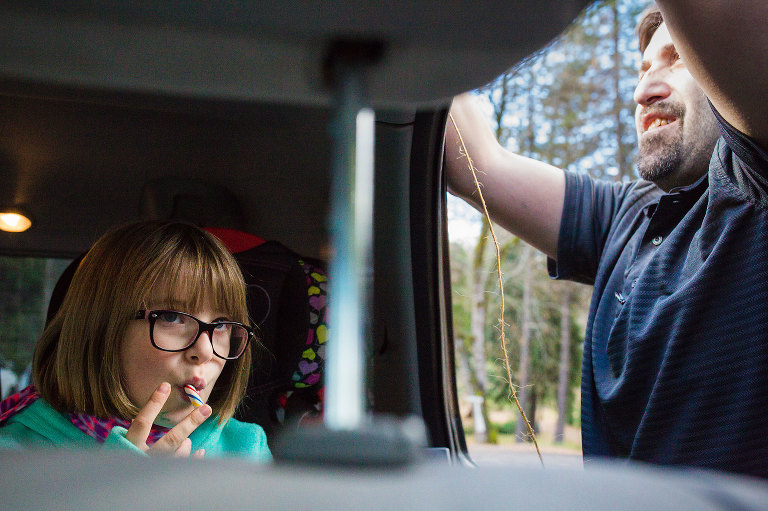 father securing item to roof of car while girl sits in backseat - documentary family photography