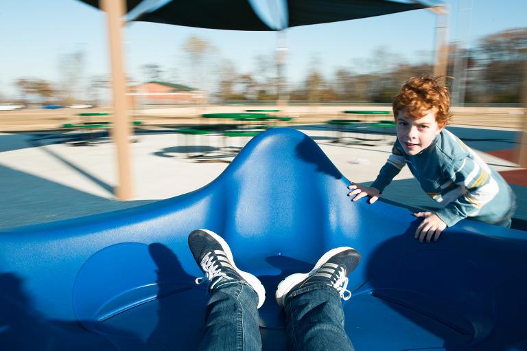 kid spinning playground equipment - documentary family photography