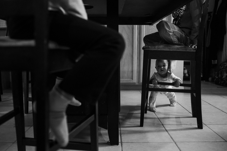 baby peering through chair legs- Documentary Family Photography