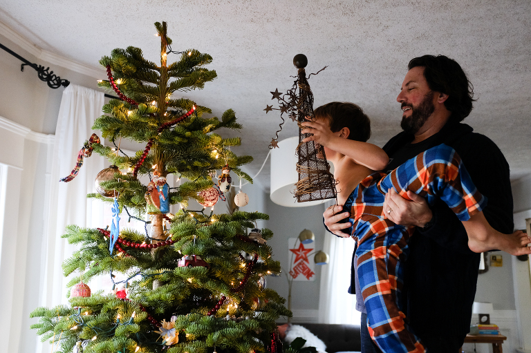 boy decorating tree with father - Documentary Family Photography
