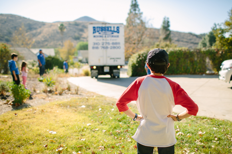 boy watching moving truck leave - Documentary Family Photography