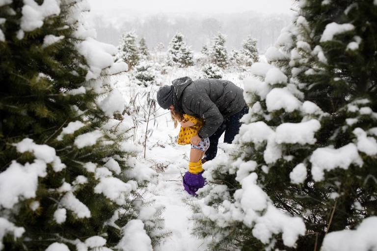 parent helps child with pants in snow - Documentary Family Photography