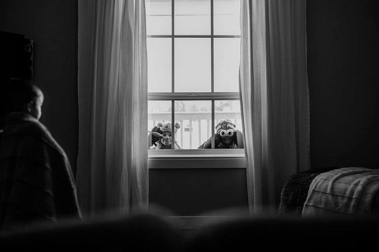 kids peer in window from outside - Documentary Family Photography