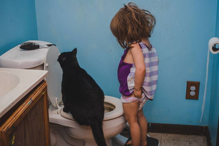 cat sits on toilet seat while girl pulls up pants - Documentary Family Photography