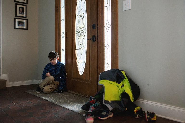 Child sits near front door - Documentary Family Photography