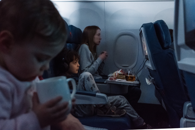 boy watching TV on plane - Documentary Family Photography