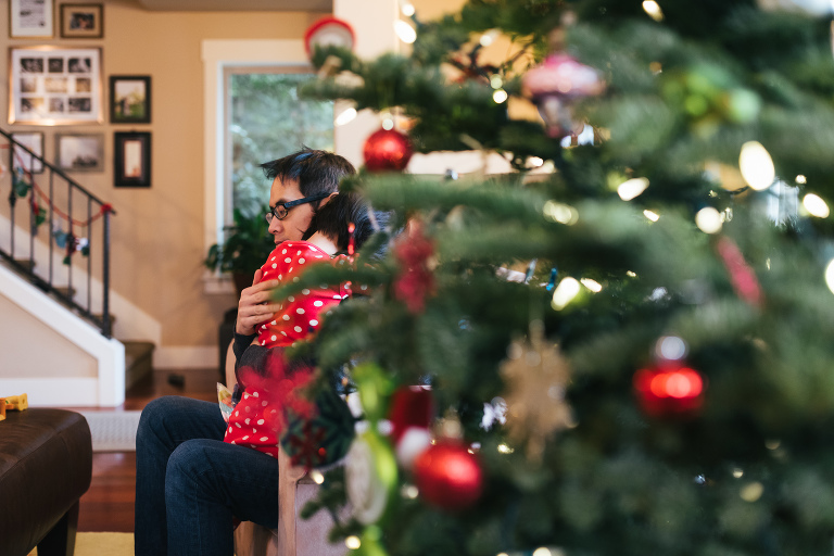father hugging child near Christmas tree - Documentary Family Photography