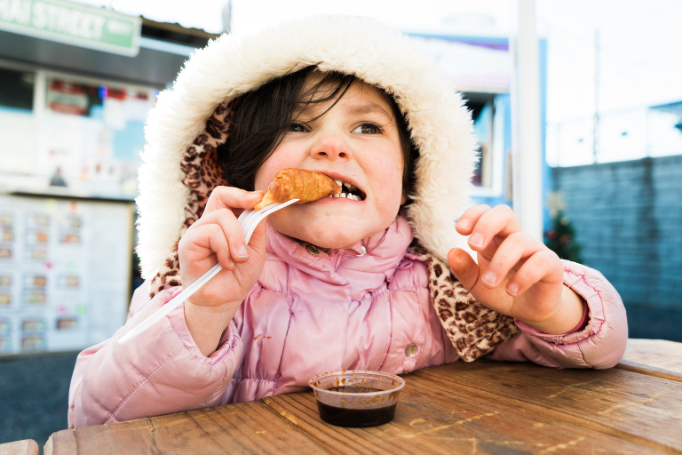 girl in coat eating - Documentary Family Photography
